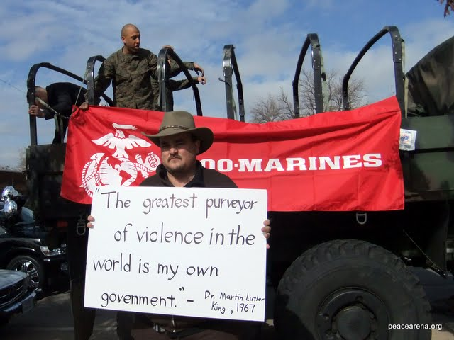 James M. Branum stands beside a Marines truck holding a sign with a quote from Martin Luther King Jr. Branum's group, the Oklahoma Center for Conscience, and the Marines were both participating in the 2011 King Holiday Parade in Oklahoma City.